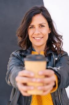 Visão vertical de mulher adulta bebendo uma xícara de café reciclada ao ar livre.