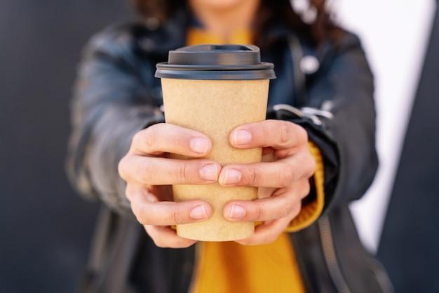 Visão vertical de mulher irreconhecível bebendo uma xícara de café reciclada ao ar livre.