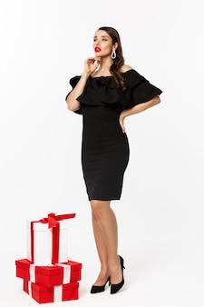 Visão vertical de mulher jovem e bonita em um vestido luxuoso, lábios vermelhos e joias, em pé com os presentes de natal em fundo branco, em pé sobre fundo branco.