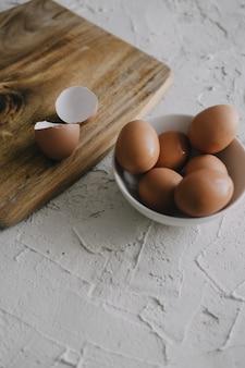 Visão vertical de ovos em uma tigela ao lado de uma tábua de cortar na mesa