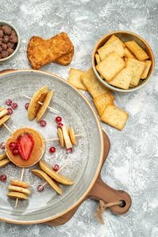 Visão vertical de panquecas e biscoitos caseiros na tábua de madeira no fundo azul