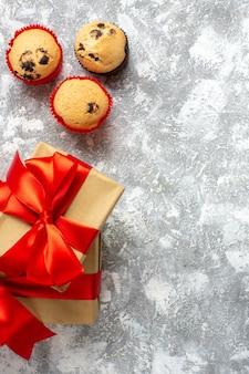 Visão vertical de pequenos cupcakes de presentes de natal com fita vermelha na superfície do gelo