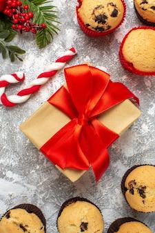 Visão vertical de pequenos cupcakes, presentes de natal com fita vermelha e ramos de abeto doce na mesa de gelo