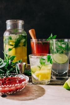 Visão vertical de refrigerantes feitos na hora com frutas e hortelã na mesa