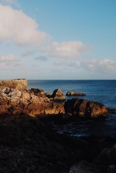 Visão vertical de rochas ao nascer do sol com o oceano ao fundo