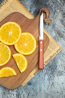 Visão vertical de rodelas de limão frescas com faca na tábua de madeira no jornal sobre fundo cinza