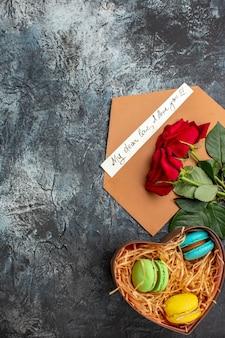 Visão vertical de rosas vermelhas e envelope com carta de amor e diferentes macarons em um fundo escuro glacial