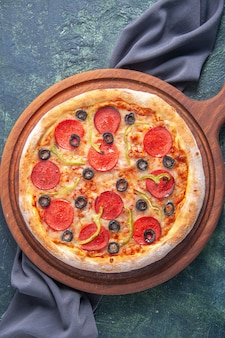 Visão vertical de saborosa pizza caseira em uma placa de madeira em uma toalha de cor escura em uma superfície escura isolada