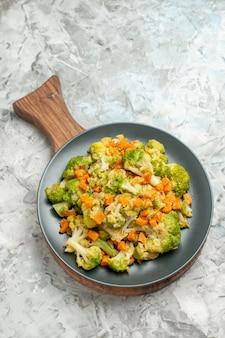Visão vertical de salada de legumes fresca e saudável em uma tábua de madeira em fundo branco