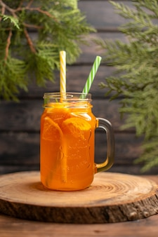 Visão vertical de suco de laranja fresco em um copo com tubo em uma bandeja de madeira em fundo marrom