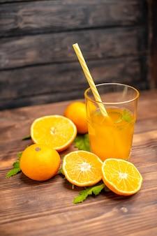 Visão vertical de suco de laranja fresco em um copo servido com tubo de hortelã e laranjas inteiras cortadas no lado esquerdo em uma mesa de madeira