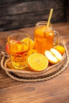 Visão vertical de suco orgânico fresco em uma garrafa e um copo servido com tubo e frutas em uma tábua de cortar e em uma mesa de madeira marrom