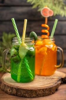 Visão vertical de sucos de frutas frescas em um copo servido com tubos em uma tábua de madeira sobre uma mesa marrom