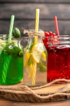 Visão vertical de sucos naturais de frutas orgânicas em garrafas servidas com tubos em uma tábua de madeira