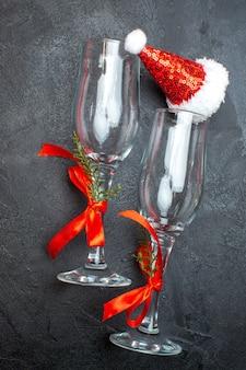 Visão vertical de taças de vidro do chapéu de papai noel de natal na superfície vermelha e preta