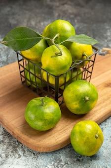 Visão vertical de tangerinas verdes com folhas dentro e fora de uma cesta na tábua de madeira na mesa cinza