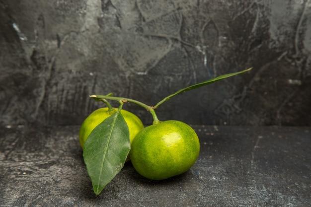 Visão vertical de tangerinas verdes frescas com folhas em fundo cinza