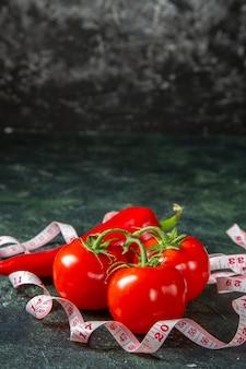 Visão vertical de tomates frescos, pimentas vermelhas e medidor na superfície de cores escuras com espaço livre