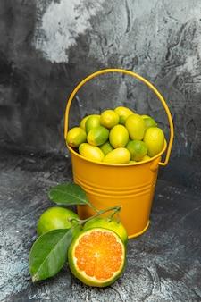 Visão vertical de um balde amarelo cheio de tangerinas verdes frescas e tangerinas cortadas pela metade em fundo cinza
