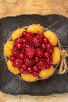 Visão vertical de um bolo de presente com frutas em fundo de cor mista