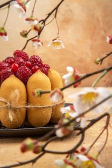 Visão vertical de um bolo de presente com frutas no lado direito de um fundo de cor mista