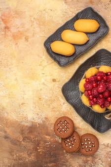 Visão vertical de um bolo de presente e biscoitos em pratos marrons em fundo de cor mista