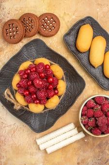Visão vertical de um bolo de presente e biscoitos em pratos marrons frutas em fundo de cor mista