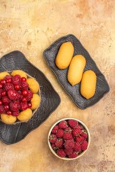 Visão vertical de um bolo de presente e biscoitos em um prato marrom em fundo de cor mista