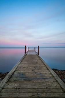 Visão vertical de um longo cais de madeira perto do oceano sob o céu de cor pastel