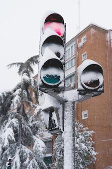 Visão vertical de um semáforo coberto de neve na rua.