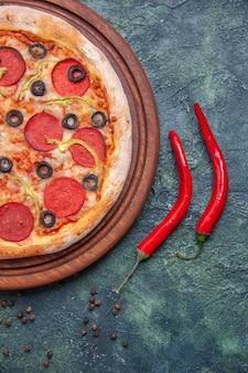 Visão vertical de uma deliciosa pizza na tábua de madeira e pimentão vermelho na superfície escura isolada