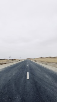 Visão vertical de uma estrada estreita no meio do campo sob um céu claro