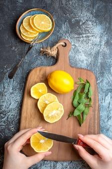 Visão vertical de uma mão cortando limões frescos e hortelã em uma tábua de madeira em fundo escuro