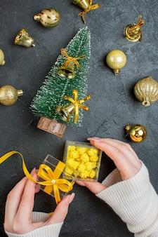 Visão vertical de uma mão segurando caixas de presentes e acessórios de decoração para árvores de natal em fundo escuro