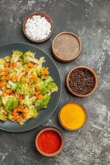 Visão vertical de uma refeição de vegetais com brocoli e cenoura em uma placa preta e especiarias na mesa cinza