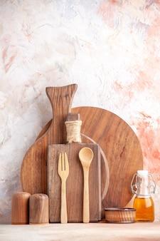 Visão vertical de várias tábuas de corte, colheres de madeira, frasco pequeno de óleo na superfície colorida