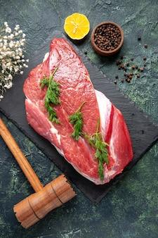 Visão vertical de verde em talheres de carne crua vermelha fresca definida na placa de corte e martelo de madeira de limão de pimenta no fundo de cor verde preto mix