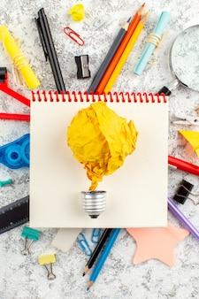 Visão vertical do balão rasgado pelo tempo no caderno espiral fechado e vários aparelhos de escritório na superfície branca