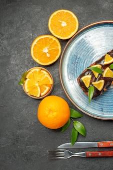 Visão vertical do conjunto de bolos saborosos amarelos inteiros e cortados com garfo e faca na mesa escura