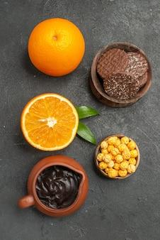 Visão vertical do conjunto de laranjas frescas e biscoitos cortados ao meio em fundo escuro