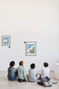Visão vertical grande angular em um grupo diversificado de crianças sentadas no chão na galeria de arte moderna e discutindo pinturas, copie o espaço