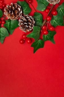 Visco e pinhas na mesa vermelha