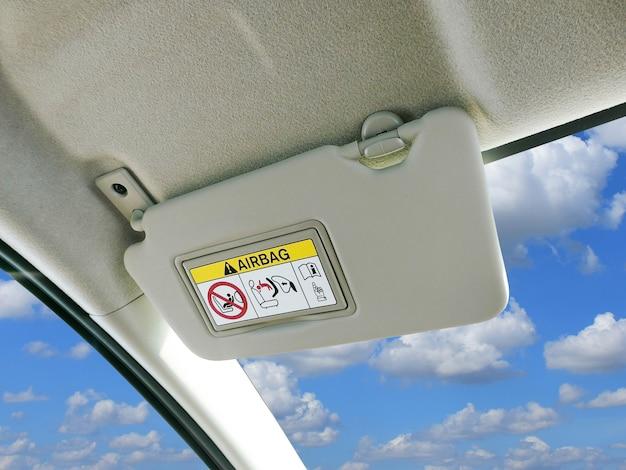 Viseira de sol do carro e sinais de advertência do sistema da bolsa a ar no carro.