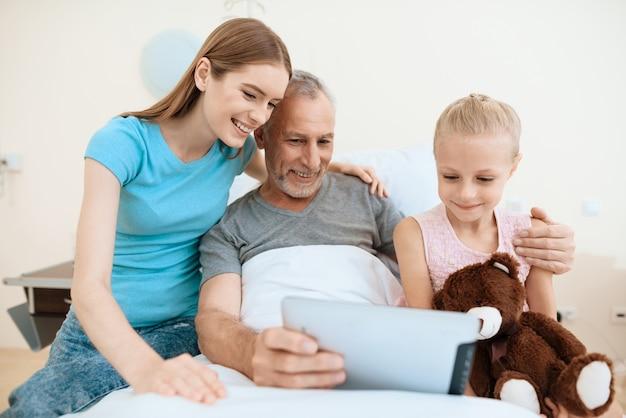 Visita familiar ao homem idoso que usa tablet