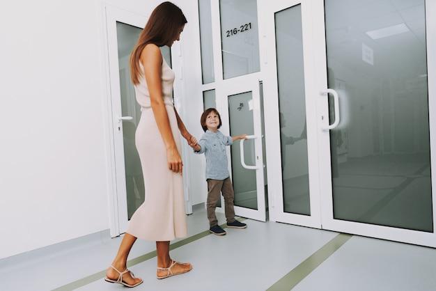 Visitando a clínica pediátrica mãe e o menino de porta aberta