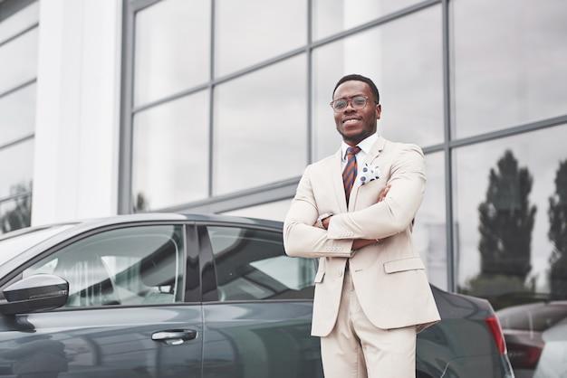Visitando concessionária de automóveis. homem de negócios preto casual de terno perto do carro.