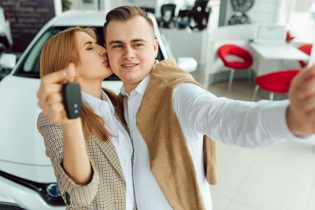 Visitando concessionária de automóveis. lindo casal está segurando a chave do carro novo e sorrindo, a garota está beijando o marido na bochecha