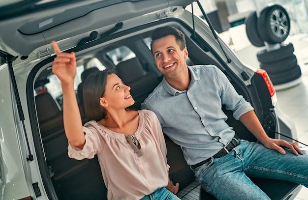 Visitando concessionária de automóveis. lindo casal está sentado no porta-malas aberto de seu carro novo e sorrindo.