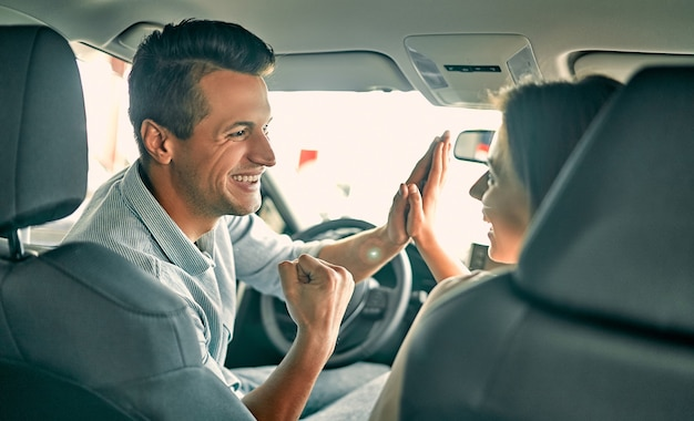 Visitando concessionária de automóveis. lindo casal olhando para a câmera e dando cinco um ao outro enquanto estão sentados em seu carro novo