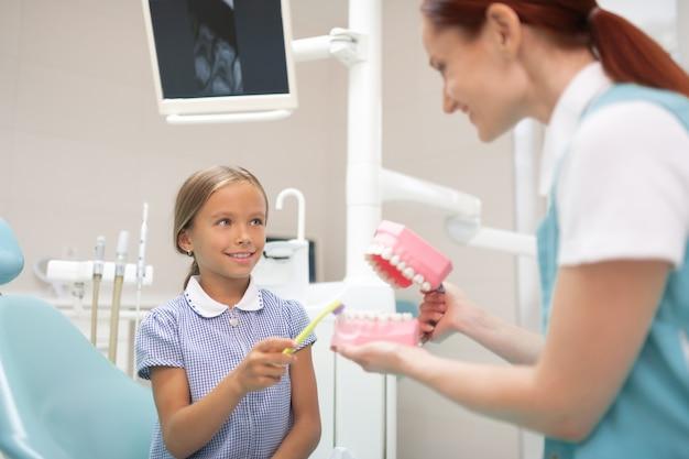 Visitando um dentista legal. linda garota sorrindo ao visitar um dentista legal depois da escola